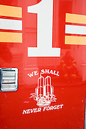 A New York fire fighter resting can be seen in the reflection of a New York fire engine door that displays a 9/11 tribute sticker
