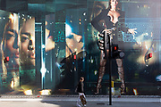 With a further 184 reported UK Covid deaths in the last 24 hrs, a total now of 43,414, a lady looks at a billboard during the construction of a new Versace store on New Bond Street during the Covid pandemnic lockdown, now easing after three months of the Stay At Home policy but now being relaxed as the shops re-open, on 26th June 2020, in London, England. Government restrictions on the 2 metre rule is to be realxed on 4th July and replaced with 'one metre plus' in the hope it stimulates the struggling UK economy.
