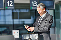 Mature businessman smiling while using smartphone in airport