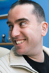 Man with a hearing aid smiling,