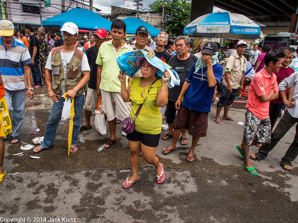 """07 AUGUST 2014 - BANGKOK, THAILAND:       People wait for a food distribution to start at Pek Leng Keng Mangkorn Khiew Shrine. Thousands of people lined up for food distribution at the Pek Leng Keng Mangkorn Khiew Shrine in the Khlong Toei section of Bangkok Thursday. Khlong Toei is one of the poorest sections of Bangkok. The seventh month of the Chinese Lunar calendar is called """"Ghost Month"""" during which ghosts and spirits, including those of the deceased ancestors, come out from the lower realm. It is common for Chinese people to make merit during the month by burning """"hell money"""" and presenting food to the ghosts. At Chinese temples in Thailand, it is also customary to give food to the poorer people in the community.    PHOTO BY JACK KURTZ"""