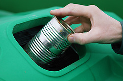 Putting steel can in the recycle bank at the Tipsmart recycling centre at Calverton,