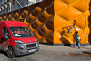 A Royal Mail van drives past the temporary renovation hoarding of luxury brand Louis Vuitton in New Bond Street, on 25th February 2019, in London, England.