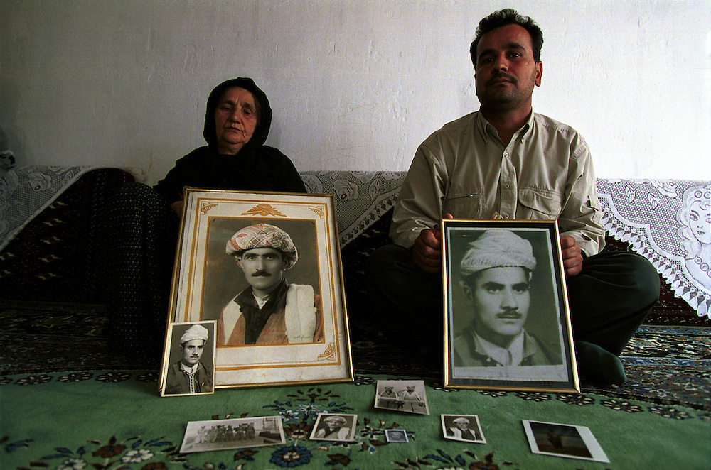 """Sef Abdullah (left) and her son Amjad Badin Mohammad holding pictures of their family """"disappeared"""" by Saddam Hussein's regime during his """"Anfal"""" campaign.  In 1982-83 the regime rounded up an estimated 200,000 Kurds who have never been seen since. Sef Abdullah lost her husband, six of her seven sons and her two sons-in-law. Her youngest son, Amjad Badin Mohammad, is the only male survivor of her family...Hamdela, Iraqi Kurdistan. 16/11/2002...Photo © J.B. Russell"""