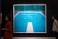 "© Licensed to London News Pictures. 23/07/2020. LONDON, UK. Staff members next to ""Pool on a Cloudy Day with Rain (Paper Pool 22) (1978) by David Hockney, estimate: £4-6 million. Preview of works on display at Sotheby's London ahead of a one-off auction on July 28.  Titled 'Rembrandt to Richter', the sale will offer the very best from Old Masters, Impressionist & Modern Art, Modern & Post-War British Art and Contemporary Art.  The exhibition is open to the public at Sotheby's New Bond Street galleries until July 28. [Image embargoed for release until 9am BST 24 July 2020].  Photo credit: Stephen Chung/LNP"