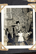 vintage image of mother posing with child in front of house