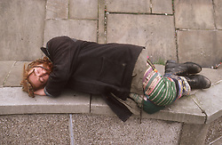 Homeless man sleeping rough on stone bench in street,