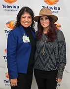 """Telenovela actress Dulce Maria, right, and Dr. Altagracia Guerrero, left, pose for a photograph following a Televisa Foundation """"Live the Dream"""" event at Burbank Middle School, December 9, 2013."""