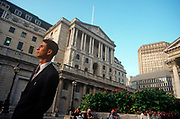 A 1990s businessman stands beneath the tall architecture of the Bank of England, in the City of London (aka The Square Mile), the capital's financial centre, on 21st June 1997, in London, England.  (Photo by Richard Baker / In Pictures via Getty Images)