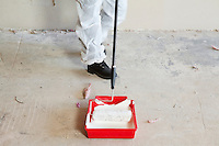 Low section of female worker with paint roller and tray