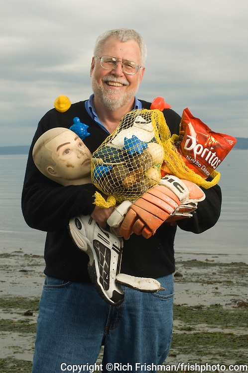 Photograph of oceanographer and environmentalist Curtis Ebbesmeyer, PhD, with some of the debris that has floated into his collection of ocean-borne trash. Ebbesmeyer uses flotsam to help track ocean currents. Much of the debris he has collected has floated thousands of miles across the Pacific, landing on farflung shores. Some has been part of the huge raft of floating garbage in the North Pacific Gyre. He is shown at Golden Gardens Park along the shore of Puget Sound in Seattle...©Rich Frishman.