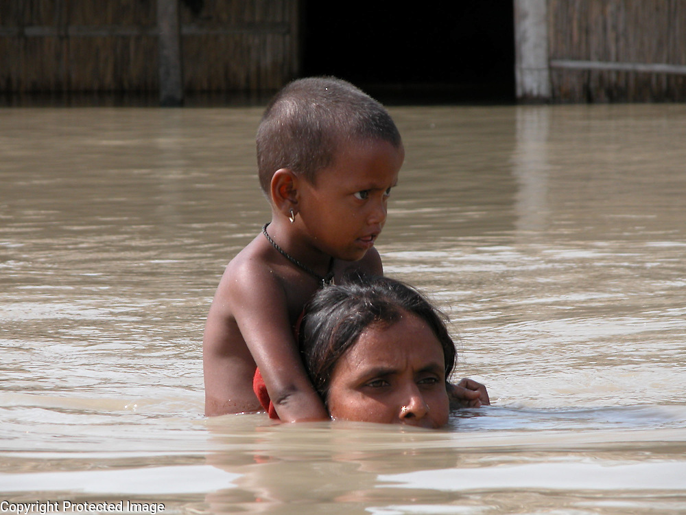 Flood victim Bangladeshi immigrant, Monowara Khatun is carrying her afraid child, Moklesa Khatun (3) to a safer place after her house is submerged by floodwaters at Nagbhangi village, about 314 kilometers southwest of Gauhati, capital of northeastern Indian state of Assam, Wednesday, July 14, 2004. .Floodwaters of the Asia's one of the largest river, Brahmaputra and its 35 tributaries have affected more than one million in all of Indian subcontinent and disrupted communication in many parts of the India and Bangladesh, sources said. (AP Photo/ Shib Shankar Chatterjee).