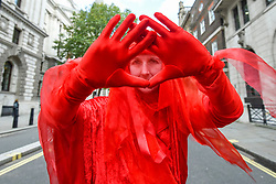 © Licensed to London News Pictures. 08/10/2019. LONDON, UK.  A member of the climate activist supporting Red Brigade stages a solo protest next to Parliament Square, on day two of Extinction Rebellion's protest which is planned to close-down Westminster and other areas in the capital for two weeks.  Demonstrators are calling on the Government's immediate action to tackle the negative effects of climate change.  Photo credit: Stephen Chung/LNP