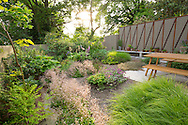 Saxifraga umbrosa, Sesleria autumnalis, Darmera peltata, Rodgersia aesculifolia, Geum 'Savannah Sunset', Digitalis purpurea, Lamium maculatum 'Beacon Silver', Osmunda regalis, wooden table and benches on patio, timber and metal screen
