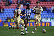 Sheyi Ojo of Wigan Athletic gets in between Gaetano Berardi and Luke Murphy of Leeds United. Skybet football league championship match , Wigan Athletic v Leeds Utd at the DW Stadium in Wigan, Lancs on Saturday 7th March 2014.<br /> pic by Chris Stading, Andrew Orchard sports photography.