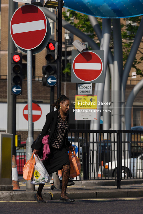Lone woman struggles across a busy east London road laden with her supermarket shopping bags.