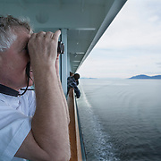 George Twarski looks enjoys the view of the Inside Passage from his private balcony on board the Norwegian Pearl, a cruise ship of Norwegian Cruise Line at Glacier Bay National Park.  Photography Jose More <br />  MR Model Release