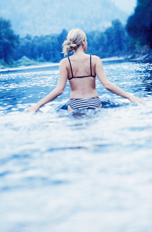 Blond woman gracefully wades into the calm waters of a river.