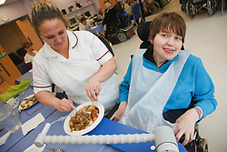 Carer cutting up lunch for young disabled client who has Cerebral Palsy at a resource for people with physical and sensory impairment.
