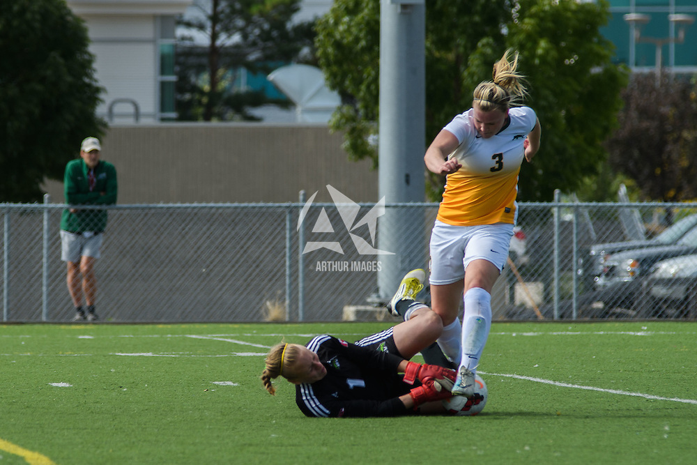 5th year defender Kayla McDonald (3) of the Regina Cougars takes a shot on goalkeeper Kayla Klim (1) of the Fraser Valley Cascades during the Women's Soccer Homeopener on September 10 at U of R Field. Credit: Arthur Ward/Arthur Images