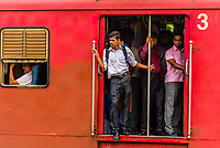 Passengers riding with doors open on a commuter train, Colombo, Sri Lanka.