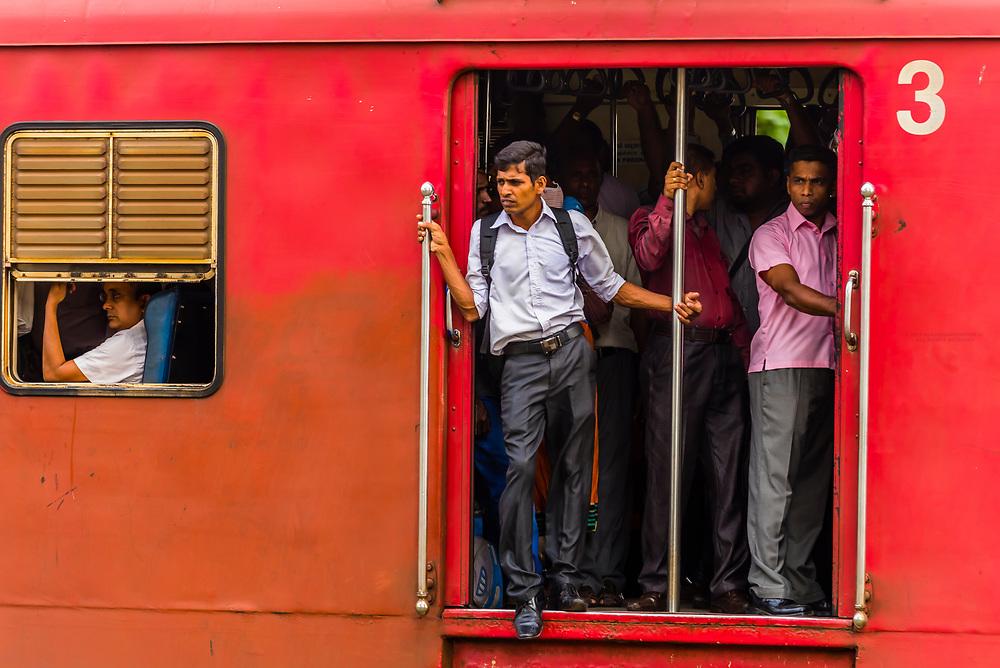 Passengers riding with doors open on a commuter train, Colombo, Sri Lanka.