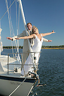 Bride and Groom having fun on the bow of the sailboat.