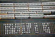 Parking lot filled with shipping crates and imported cars off-loaded from cargo ships.