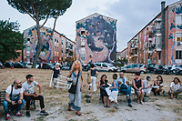 """ROME, ITALY - 27 JUNE 2017: Spectators bring their own chairs to watch the premiere of """"Don Giovanni OperaCamion"""", an open-air opera performed on a truck in San Basilio, a suburb in Rome, Italy, on June 27th 2017.<br /> <br /> Director Fabio Cherstich's idae of an """"opera truck"""" was conceived as a way of bringing the musical theatre to a new, mixed, non elitist public, and have it perceived as a moment of cultural sharing, intelligent entertainment and no longer as an inaccessible and costly event. The truck becomes a stage that goes from square to square with its orchestra and its company of singers in Rome. <br /> <br /> """"Don Giovanni Opera Camion"""", after """"Don Giovanni"""" by Wolfgang Amadeus Mozart is a new production by the Teatro dell'Opera di Roma, conceived and directed by Fabio Cherstich. Set, videos and costumes by Gianluigi Toccafondo. The Youth Orchestra of the Teatro dell'Opera di Roma is conducted by Carlo Donadio."""