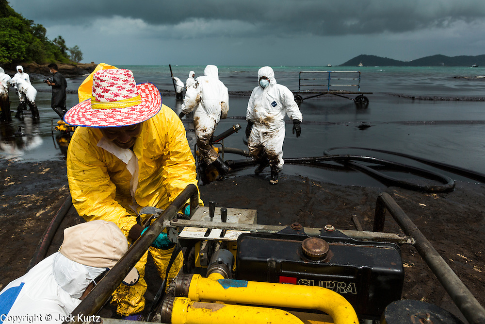 30 JULY 2013 - KOH SAMET, RAYONG, THAILAND: Workers prepare to pump oil out of the surf on Ao Prao island on Koh Samet island. About 50,000 liters of crude oil poured out of a pipeline in the Gulf of Thailand over the weekend authorities said. The oil made landfall on the white sand beaches of Ao Prao, on Koh Samet, a popular tourists destination in Rayong province about 2.5 hours southeast of Bangkok. Workers from PTT Global, owner of the pipeline, and up to 500 Thai military personnel are cleaning up the beaches. Tourists staying near the spill, which fouled Ao Prao beach, were evacuated to hotels on the east side of the island, which was not impacted by the spill. PTT Global Chemical Pcl is part of state-controlled PTT Pcl, Thailand's biggest energy firm.      PHOTO BY JACK KURTZ