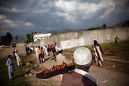 An elderly man sells pastries to a gathering crowd of onlookers outside the compound where Osama Bin Laden was killed in an operation by US Navy Seals, on May 4, 2011, in Abottabad, Pakistan.  The operation, code-named Operation Neptune Spear, was launched from neighbouring Afghanistan by Seal Team Six. U.S. forces took bin Laden's body to Afghanistan for identification, then dumped it the Arabian Sea. Pakistan has since been widely suspected as having prior knowledge of his whereabouts as the compound was less than a kilometre from the country's biggest military academy. Osama bin Laden was allegedly responsible for supporting the bombing of the US Embassy in Nairobi, Kenya, the attack on the USS Cole and the suicidal attacks of September 11, 2001 in the US. (Photo by Warrick Page)