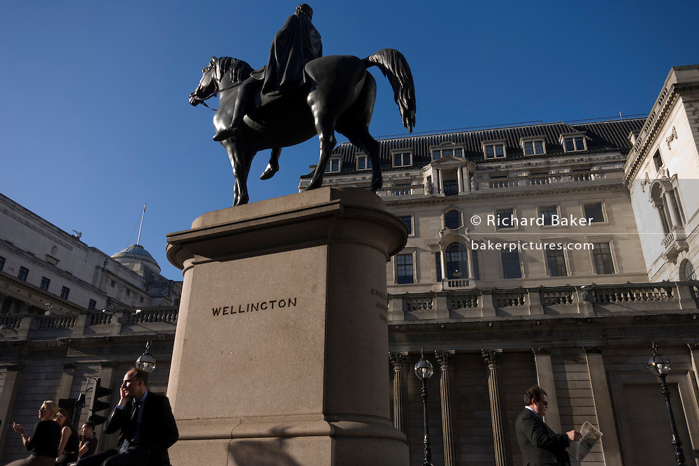 Businessmen beneath the statue of the Duke of Wellington in Bank triangle in the City of London.