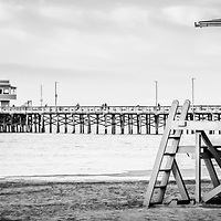 Newport Pier and lifeguard tower 19 panorama picture in black and white. Panoramic photo ratio is 1:3. Newport Pier is in Newport Beach which is an affluent coastal city in Orange County Southern California.