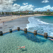 Built in 1947, the Ross Jones Memorial Pool is a popular outdoor swimming area beside Coogee Beach. <br /> <br /> Waves from the ocean spill over the concrete walls of the baths during high tide.