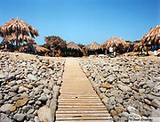 Wooden pathway surrounded by pebbles leading up to some beach huts Cala Jondial Beach, Ibiza 2000