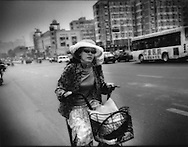 Encounter with a veiled woman passing by on a bicycle, Central Tianjin, China.