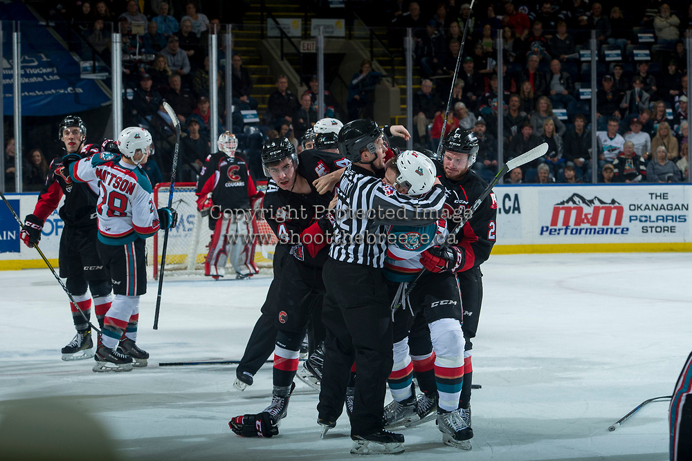 KELOWNA, CANADA - MARCH 14: Linesman Dustin Minty gets between Joel Lakusta #4 of the Prince George Cougars and Carsen Twarynski #18 of the Kelowna Rockets during a third period line brawl on March 14, 2018 at Prospera Place in Kelowna, British Columbia, Canada.  (Photo by Marissa Baecker/Shoot the Breeze)  *** Local Caption ***