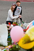 "15 JANUARY 2011 - TUCSON, AZ: A woman comforts her son at the memorial on the lawn in front of the University Medical Center in Tucson, AZ, Saturday, January 15. The memorial has been growing since the mass shooting last week. Six people were killed and 14 injured in the shooting spree at a ""Congress on Your Corner"" event hosted by Congresswoman Gabrielle Giffords at a Safeway grocery store in north Tucson on January 8. Congresswoman Giffords, the intended target of the attack, was shot in the head and seriously injured in the attack. She is hospitalized at UMC. The alleged gunman, Jared Lee Loughner, was wrestled to the ground by bystanders when he stopped shooting to reload the Glock 19 semi-automatic pistol. Loughner is currently in federal custody at a medium security prison near Phoenix.  Photo by Jack Kurtz"