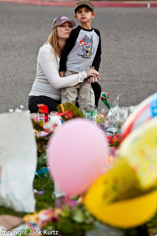 """15 JANUARY 2011 - TUCSON, AZ: A woman comforts her son at the memorial on the lawn in front of the University Medical Center in Tucson, AZ, Saturday, January 15. The memorial has been growing since the mass shooting last week. Six people were killed and 14 injured in the shooting spree at a """"Congress on Your Corner"""" event hosted by Congresswoman Gabrielle Giffords at a Safeway grocery store in north Tucson on January 8. Congresswoman Giffords, the intended target of the attack, was shot in the head and seriously injured in the attack. She is hospitalized at UMC. The alleged gunman, Jared Lee Loughner, was wrestled to the ground by bystanders when he stopped shooting to reload the Glock 19 semi-automatic pistol. Loughner is currently in federal custody at a medium security prison near Phoenix.  Photo by Jack Kurtz"""