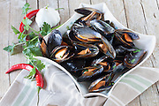 Plate with sauteed mussels decorated with fresh parsley, garlic and red chili pepper.
