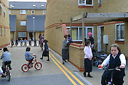 Orthodox Jewish children playing in the street of Reizel close an Agudas Israel Housing Association development for low-income Orthodox Jewish families in Stamford Hill, London.  All the children play regularly together, having bike races and playing football. There is a real sense of a community, some mothers are out with their younger children keeping an eye on goings on.
