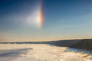 The temperature hovered at 4 below zero as the sun rose over the Illinois River. Amazing things can happen in such frigid conditions. Because of the nearly 40 degree temperature difference between the air and the water, steam formed and swirled around the river. The steam turned into ice crystals and drifted up into the air. The ice crystals then acted as prisms, refracting the light rays from the sun on the right. That is how this bright and colorful sundog was formed. This view is from Eagle Cliff at Starved Rock State Park.<br />