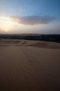 "Sunset over Liwa Oasis and the vast sand dunes of the Rub'al Khali (""Empty Quarter"")."