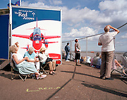 Members of the public watch or listen to the 'Red Arrows', Britain's Royal Air Force aerobatic team at Southend Air show.
