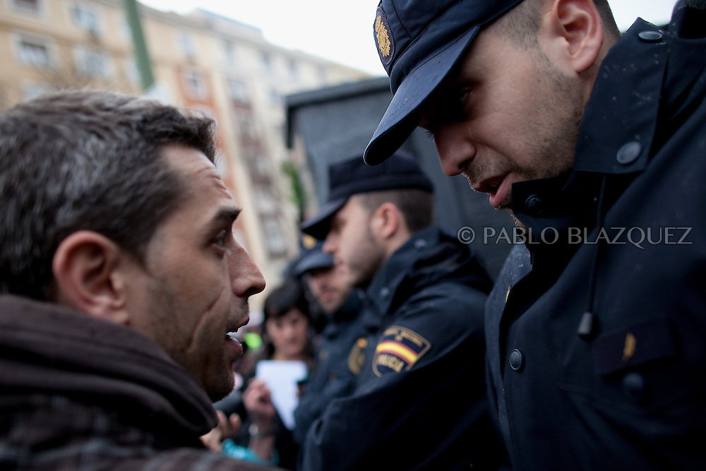 Riot police and an anti-eviction activist argue during a 'escrache' while they were going towards the house of Popular Party Deputy Mari Luz Prieto, on April 4, 2013 in Madrid, Spain. The Mortgage Holders Platform (PAH) and other anti evictions organizations are organizing 'escraches' for several weeks under the slogan 'There are lifes at risk' to claim the vote for a Popular Legislative Initiative (ILP) to stop evictions, regulate dation in payment and social rent outside Popular Party deputies' houses and offices..'Escraches' are form of peaceful public protest that was used in Argentine in 1995 to point to pardoned genocides of Argentenia's Dictatorship at their doorsteps.
