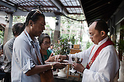 JAKARTA, INDONESIA, MARCH 2013: Yulianus Rettoblaut (Mami Yuli) in the catholic church during the Mass celebration a few days before Easter. The priest, Romo Sumardi, offers shelter and food to the waria elderly community in times of crisis.