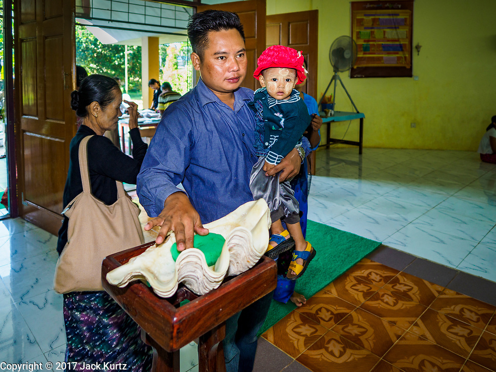 19 NOVEMBER 2017 - HWAMBI, YANGON REGION, MYANMAR: A man dips his hand into the holy water before mass in Sacred Heart's Catholic Church in Hwambi, about 90 minutes north of Yangon, before mass Sunday. Catholics in Myanmar are preparing for the visit of Pope Francis. He is coming to the Buddhist majority country November 27-30. There about 500,000 Catholics in Myanmar, about 1% of the population. Catholicism was originally brought to what is now Myanmar more than 500 years ago by Portuguese missionaries and traders.    PHOTO BY JACK KURTZ
