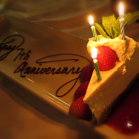 Romantic celebration - Happy Anniversary written with chocolate on a white plate with slice of cake and candles.