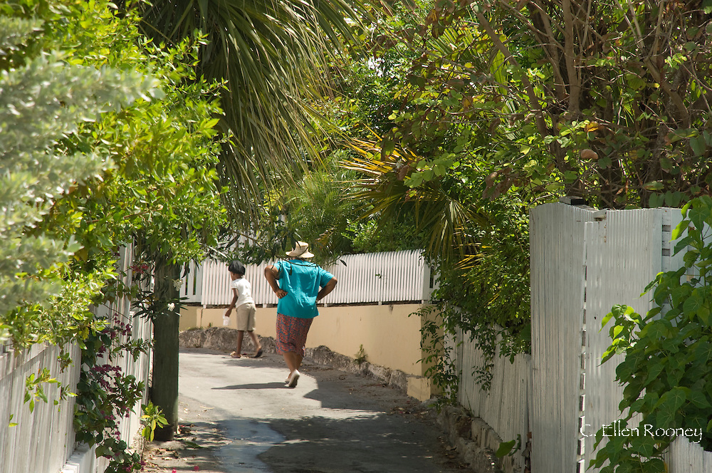 A woman and child walking down a leafy land in Dunmore Town, Harbour Island,<br /> The Bahamas