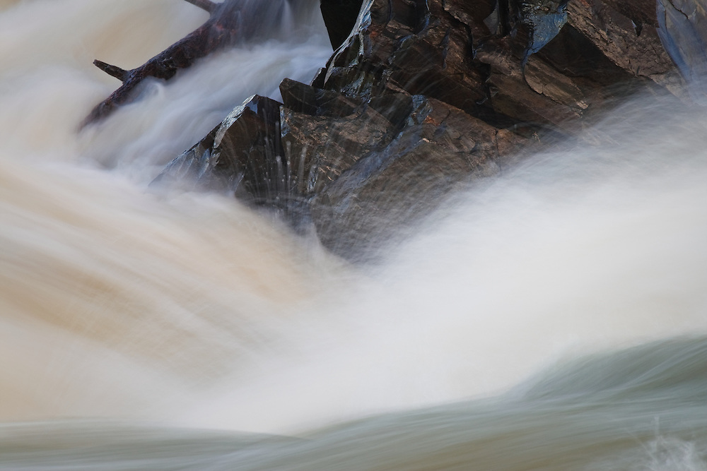 A close-up of rocks and driftwood being buffeted by the swollen Potomac River above Great Falls in January, Great Falls National Park, Great Falls, Virginia